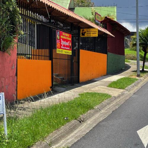 Casa color amarillo con muros anaranjados, a mano izquierda.